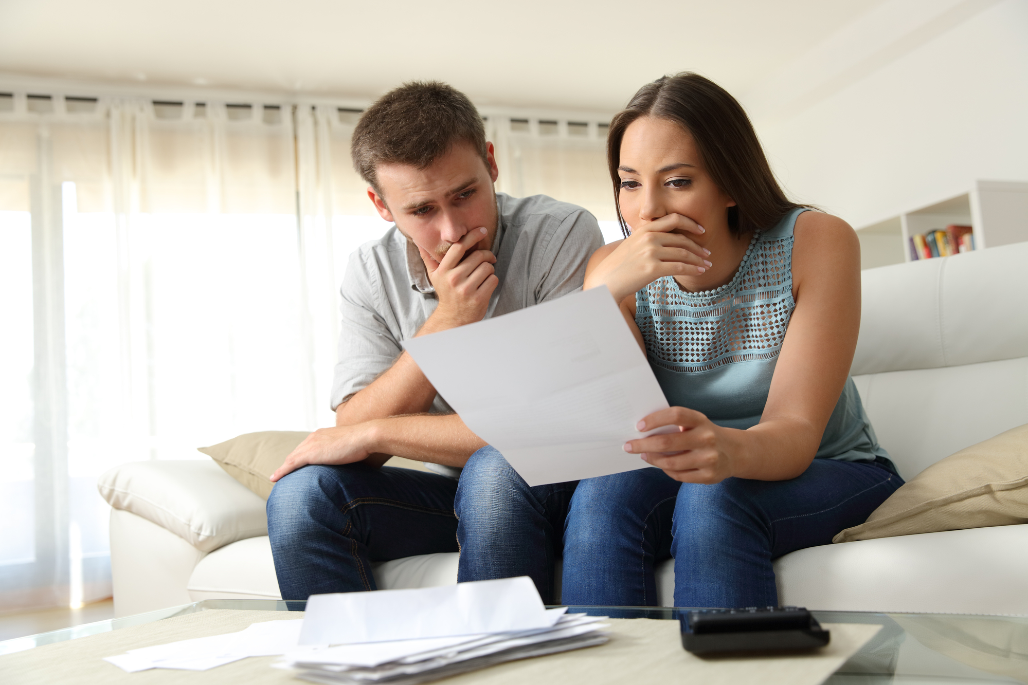 Confused couple checking bank statement